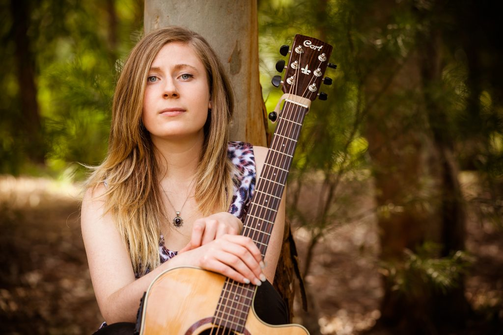 Portrait of Lily Fisher with guitar